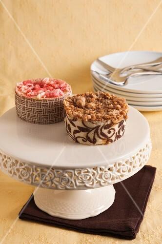 A mini strawberry cakes and a mini caramel cake on a cake stand
