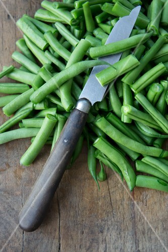 String beans with a knife on a wooden chopping board