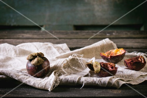 Whole and sliced mangosteens on a grey cloth on a wooden table