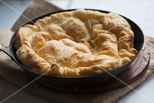 Tarte Tatin being made: freshly baked pastry on caramelised apples