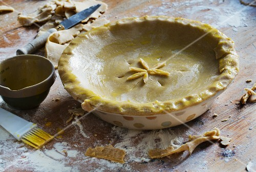 An apple and plum pie being made