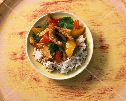 Fried pork with peppers on a bed of rice with coriander