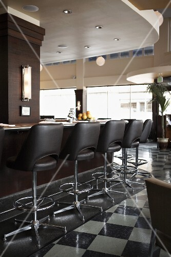 A restaurant bar with black leather stools