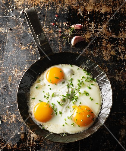 Three fried eggs with chives in a hot, black pan