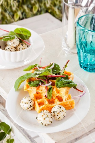 A carrot waffle with goat's cream cheese and lettuce