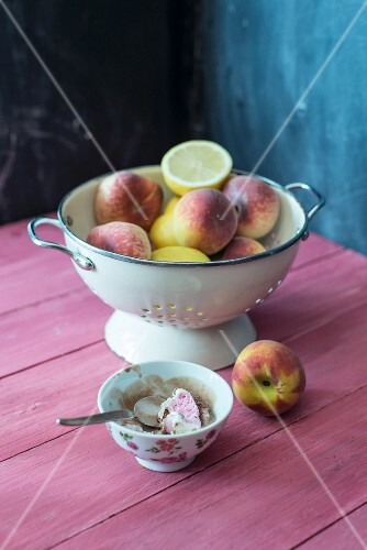 Peaches, vineyard peaches and lemons in a colander with a bowl of Neapolitan ice cream next to it