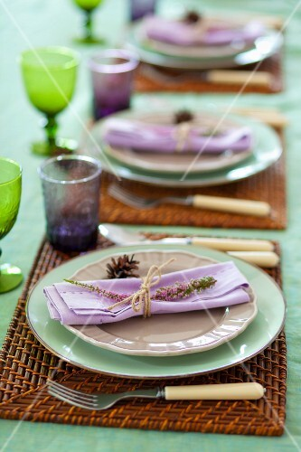 A table laid with lilac napkins decorated with flowers