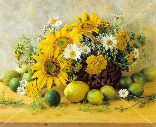 An arrangement of citrus fruits and yellow summer flowers in a wicker basket