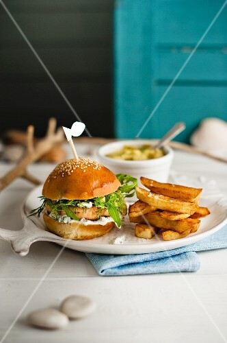 A salmon burger with dill mayonnaise, rocket, chips and homemade broad bean guacamole