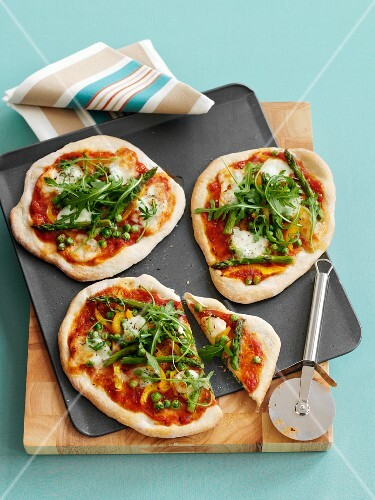 Mini pizzas with peas, green asparagus, peppers and rocket