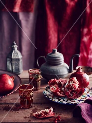 Pomegranate, tea pot and coloured glasses