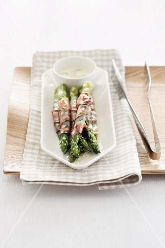 Asparagus wrapped in bacon with a dip