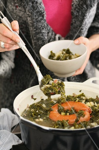 A woman ladling kale soup from a pot