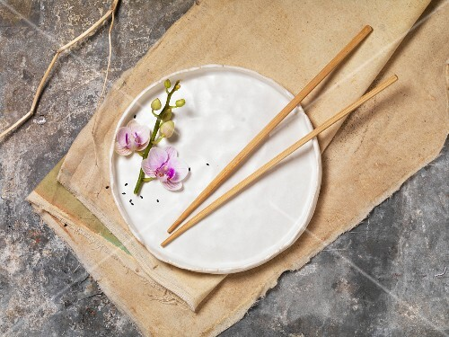 A plate decorated with chopsticks and an orchid sprig (seen from above)