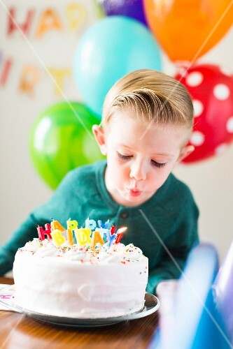 A boy blowing out candles on a birthday cake