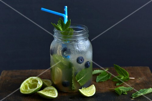 A mojito with blueberries and ice cubes