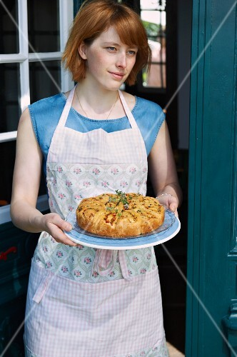 A woman serving a courgette and tomato rose cake