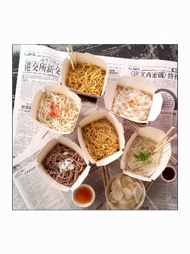 Pasta in takeaway containers on a newspapers (China)