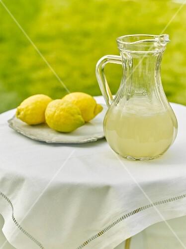 Lemonade in a jug on a table outside