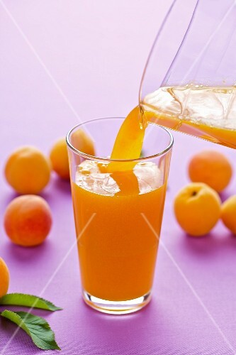 Apricot juice being poured into a glass