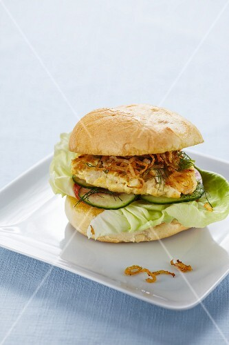 A hake burger with yoghurt and roasted onions