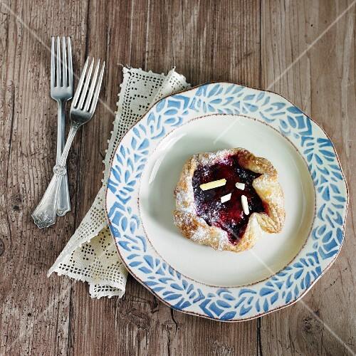 Mini cherry crostata with slivered almonds and icing sugar