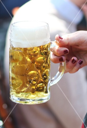 A woman holding a tankard of beer