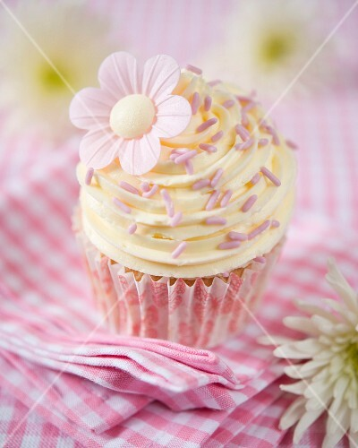 A vanilla cupcake decorated with daisies