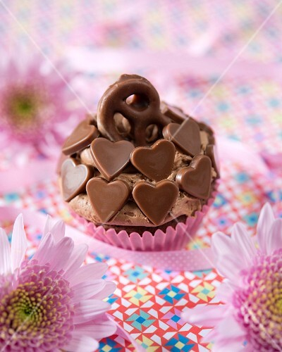 A chocolate cupcake decorated with chocolate hearts