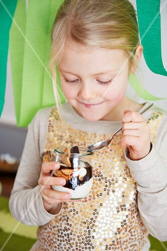 A little girl eating a quark dessert with bananas and chocolate sauce