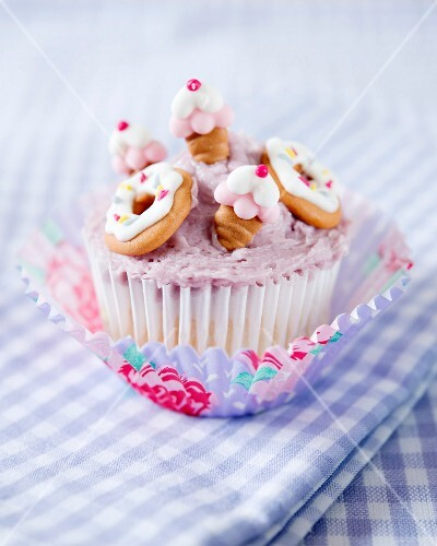 A cupcake decorated with blackcurrant butter cream and fondant cakes