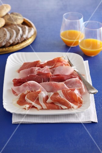 A ham platter with bread and fruit juice