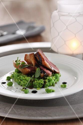 Smoked roast pork on peas with balsamic sauce