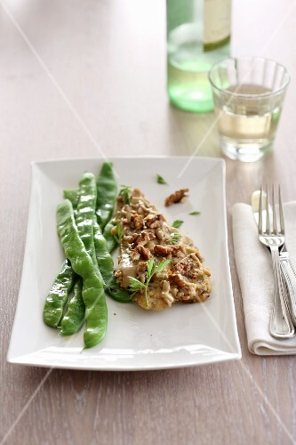 A fish fillet with tahini sauce, walnuts and a bean medley