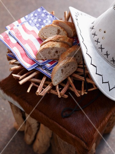 Sliced white bread with napkins and a cowboy hat on an animal hide stool