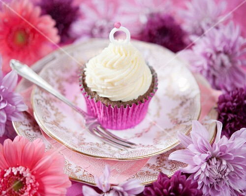 A celebratory cupcake decorated with an engagement ring