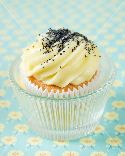 A cupcake with lemon butter cream and poppy seeds