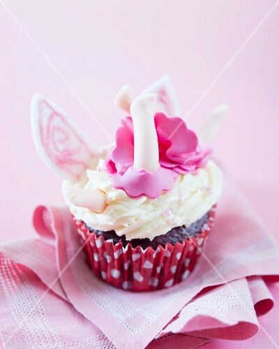A cupcake decorated with a crashed fairy in fondant and butter cream