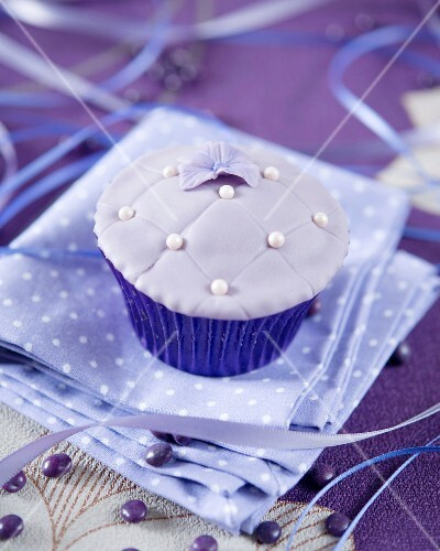 A purple fondant cupcake decorated with sugar pearls