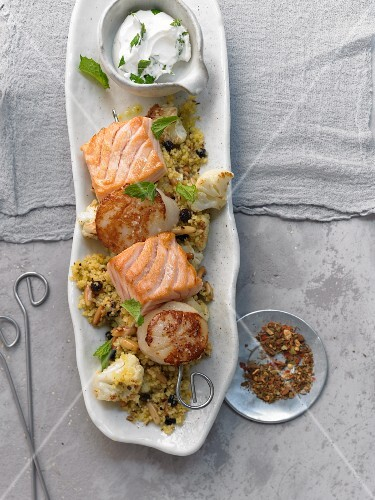 Salmon and scallops skewers on couscous with currants and pine nuts