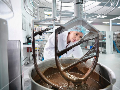 A baker mixing chocolate in a cake factory