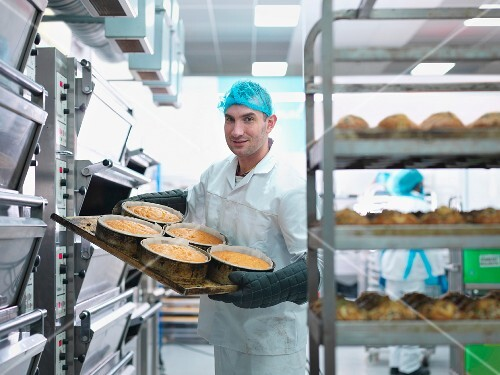 A baker taking freshly baked cakes out of the oven in a cake factory