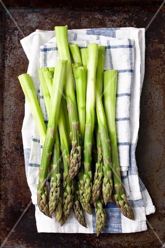 Peeled green asparagus on a tea towel