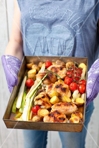 A woman serving roast chicken bits with asparagus, cherry tomatoes and potatoes