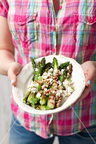 A woman holding a plate of grilled green asparagus with feta cheese and balsamic vinegar