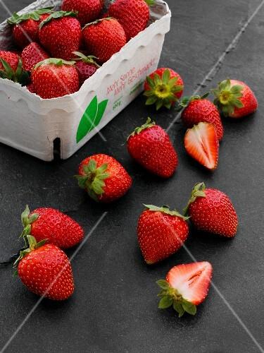 Frische Erdbeeren im Pappschälchen und daneben