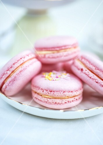 Pink macaroons filled with raspberry jam and clotted cream (close-up)
