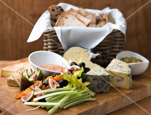 A cheese platter with vegetables, fruit and a bread basket