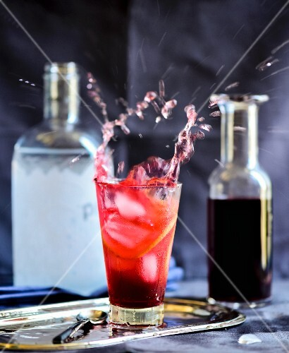 Ice cubes falling into a cocktail with hibiscus syrup and orange slices