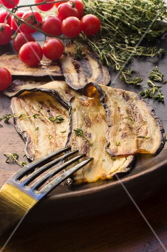 Grilled aubergine slices with thyme and cherry tomatoes on a wooden plate